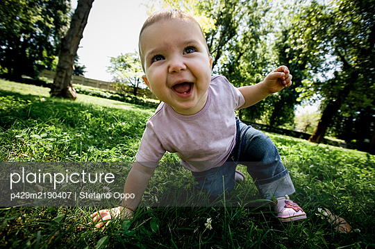 Portrait of baby girl playing on a lawn in a park, looking at camera. - p429m2190407 by Stefano Oppo