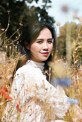 Asiatin sitzt auf Blumenwiese - p045m2204311 von Jasmin Sander