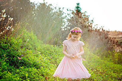 Carefree girl wearing wreath while standing amidst plants on field at park - p1166m1544988 by Cavan Social