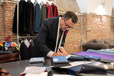 Elegant tailor drawing sketches in loft studio - p1166m2261410 by Cavan Images