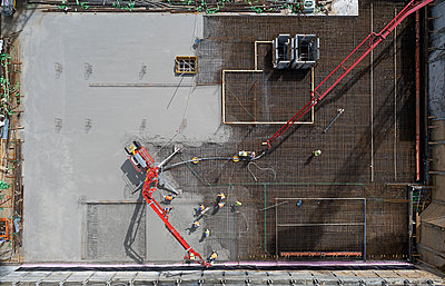 Pouring concrete, construction workers at construction site - p1292m2281019 by Niels Schubert