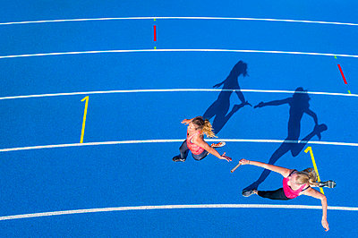 Top view of two female runners passing the baton on tartan track - p300m1537273 by Stefan Schurr
