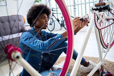 Concentrated woman with Afro hairstyle repairing bicycle at home - p300m2274819 by Giorgio Fochesato