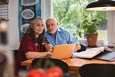 Senior couple using credit card for online payment on laptop at home - p426m1131013f by Maskot
