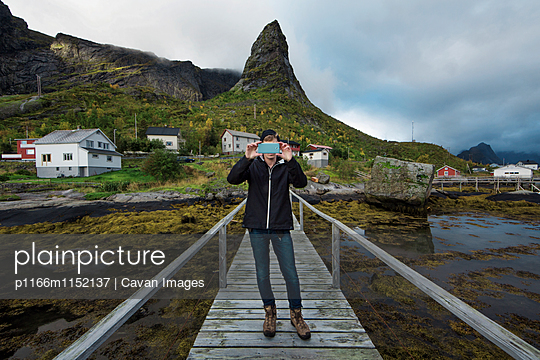 Man photographing while standing on boardwalk against mountain - p1166m1152137 by Cavan Images