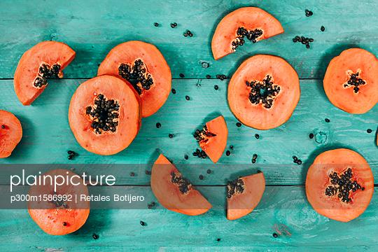 Sliced papaya on blue wood - p300m1586992 von Retales Botijero