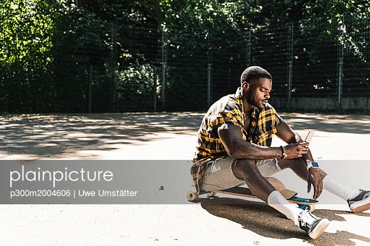 Cool young man in skate park, using smartphone - p300m2004606 von Uwe Umstätter