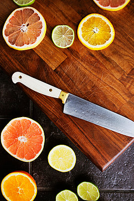 Directly above shot of sliced citrus fruits and knife on chopping board - p1185m1015791f by Astrakan