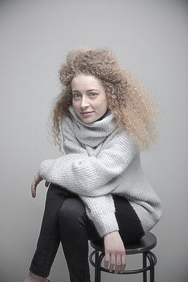 Portrait confident beautiful young woman with blonde curly hair and blue eyes - p1192m2066224 by Hero Images