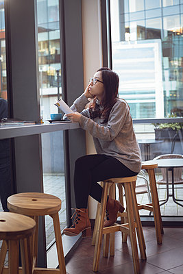 Thoughtful woman holding magazine while having coffee in cafeteria - p1315m1566105 by Wavebreak