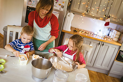Mother and kids preparing dough for Christmas cookies - p1315m2041436 by Wavebreak