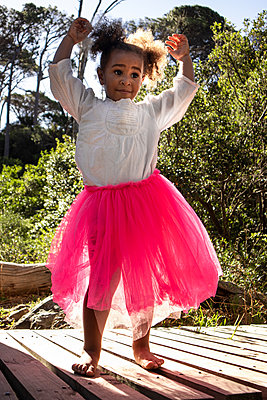 Little girl in pink tulle skirt makes dance steps - p1640m2246802 by Holly & John