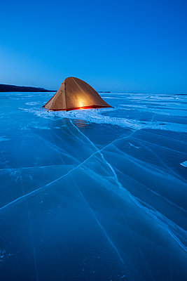 Russia, Amur Oblast, illuminated tent on frozen Zeya River at blue hour - p300m1568551 by Vasily Pindyurin