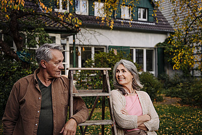 Senior couple with a ladder in garden of their home - p300m2155235 by Gustafsson