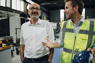 Businessman and man in reflective vest talking in a factory - p300m2170466 by Kniel Synnatzschke