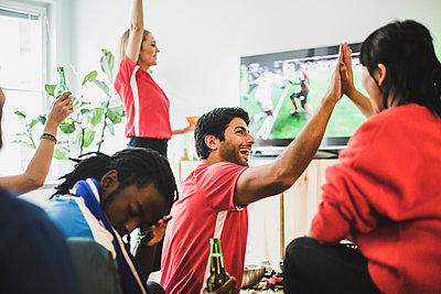 Young man sitting upset while red team celebrating victory at home - p426m2169544 by Maskot
