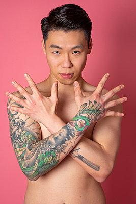 Asian man with Tattoos - p817m2159121 by Daniel K Schweitzer