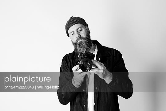 Mann mit Vollbart justiert seine Fotokamera - p1124m2229043 von Willing-Holtz