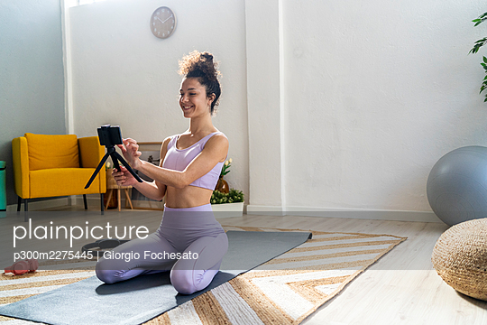 Smiling woman kneeling while touching mobile phone during vlogging at home - p300m2275445 by Giorgio Fochesato
