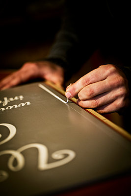 A sign writer working with a loaded brush painting a line freehand on the edge of a sign.  - p1100m1158324 by Mint Images