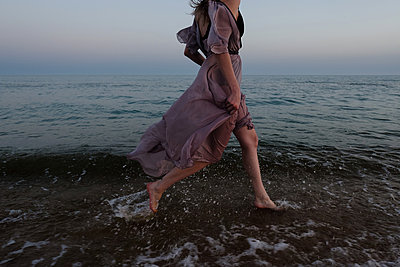 Woman running on beach - p1363m2126650 by Valery Skurydin