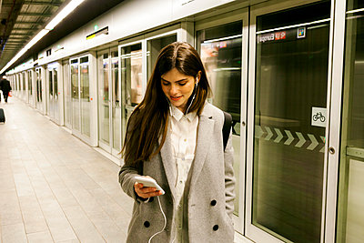 Young woman using cell phone and earphones in a passageway - p300m1587763 by Valentina Barreto