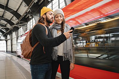 Young couple using smartphone at the station platform as the train comes in, Berlin, Germany - p300m2154534 von Hernandez and Sorokina