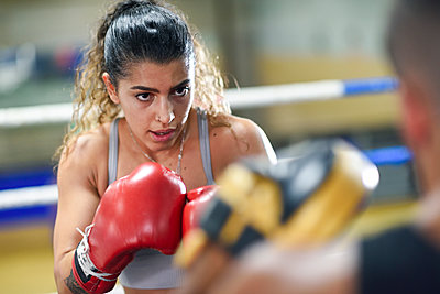 Portrait of focused female boxer sparring with her coach in gym - p300m2180878 by Javier Sánchez Mingorance