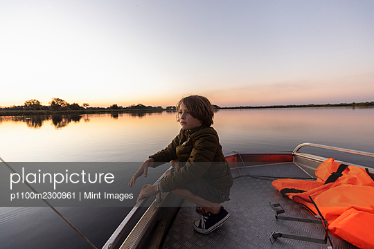 A young boy fishing from a boat on the flat calm waters of the Okavango Delta at sunset - p1100m2300961 by Mint Images