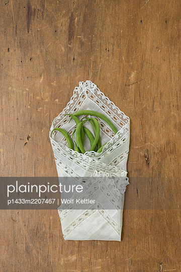 Green beans wrapped in a vintage lace handkerchief. - p1433m2207467 by Wolf Kettler