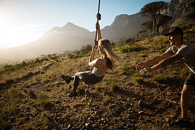 Man pushes woman on a swing - p1640m2260979 by Holly & John