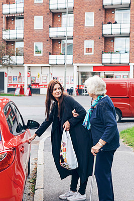 Young woman opening car door for grandmother on city street - p426m1151725 by Maskot