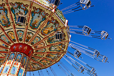 Chain swing ride against blue sky - p555m1453486 by Spaces Images