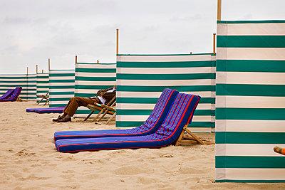 Man sitting on a beach chair between wind screens - p6070003 by Benjamin Rondel