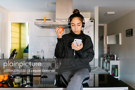 Teenage girl wearing headphone holding apple while using mobile phone at home - p300m2240332 by Ezequiel Giménez