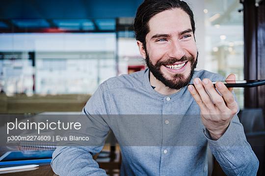 Smiling businessman talking on speaker through smart phone at work place - p300m2274609 by Eva Blanco