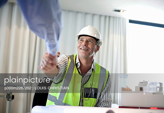 Man in hard hat and high visability (52-57) having a meeting in architect's office, Cape Town, South Africa - p300m2287262 von LOUIS CHRISTIAN