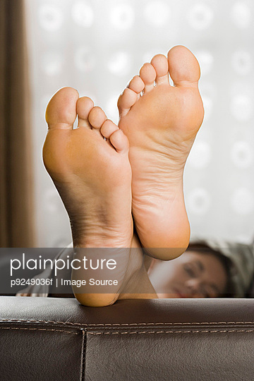 Feet of woman on sofa - p9249036f by Image Source