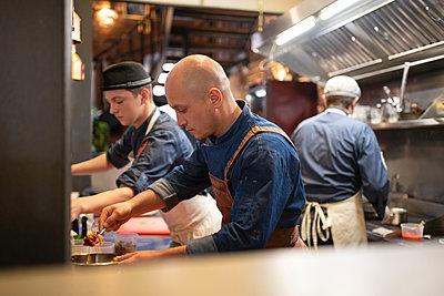Bald chef preparing pasta near team in kitchen - p1166m2250612 by Cavan Images