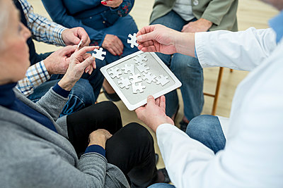 Doctor playing jigsaw puzzle with group of seniors in retirement home - p300m2207049 by Fotoagentur WESTEND61