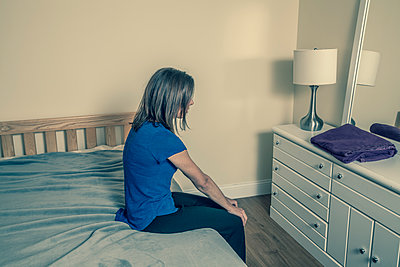 Frau sitzt auf dem Bett - p397m1515451 von Peter Glass