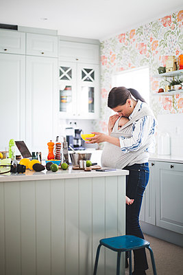 Female food blogger caring daughter while standing in kitchen at home - p426m2116978 by Maskot