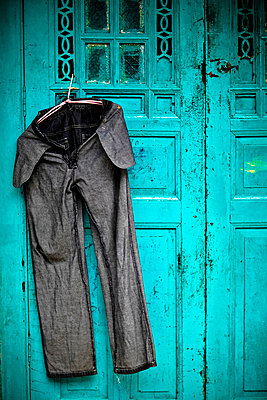 a pair of freshly washed bluejeans hangs on a blue door to dry in the midday sun; penang malaysia - p44213317f by Matt Brandon