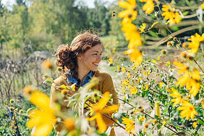 Young woman stands next to sunflower field - p586m1214254 by Kniel Synnatzschke