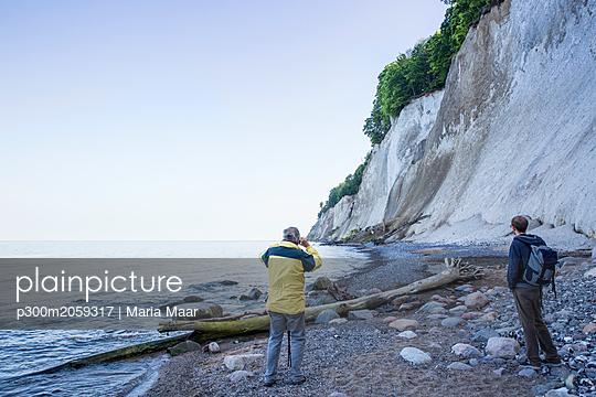Germany, Mecklenburg-Western Pomerania, Ruegen, Jasmund National Park, hikers looking on chalk cliff at 'Kieler Ufer' - p300m2059317 by Maria Maar