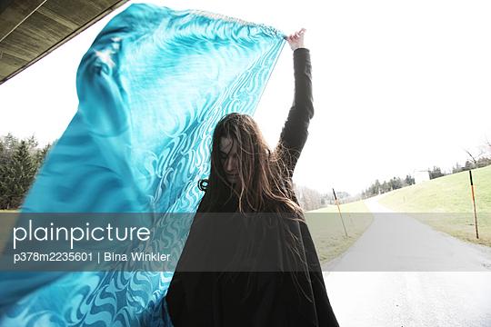 Woman waving blue fabric - p378m2235601 by Bina Winkler