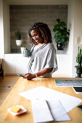 Smiling creative female designer drinking coffee and using smart phone in office - p1192m2124256 by Hero Images