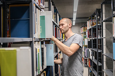 Male student at bookshelf in library - p1284m1452128 by Ritzmann