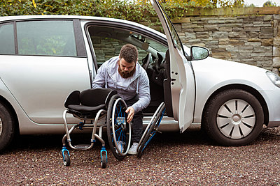 Disabled young man holding wheelchair while getting out of a car - p1315m1566292 by Wavebreak