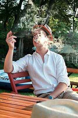 Mann raucht Zigarre im Freien - p1437m2008214 von Achim Bunz